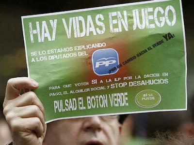 Un hombre sostiene un cartel con el lema 'Hay vidas en juego' durante una concentración de la PAH. -EFE