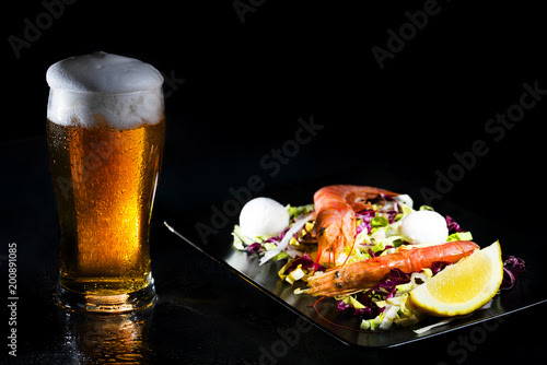 Sweated glass of cold light beer and salad with argentine red shtimp. Photo on dark background. Copy space - Acquista questa foto stock ed esplora foto simili in Adobe Stock
