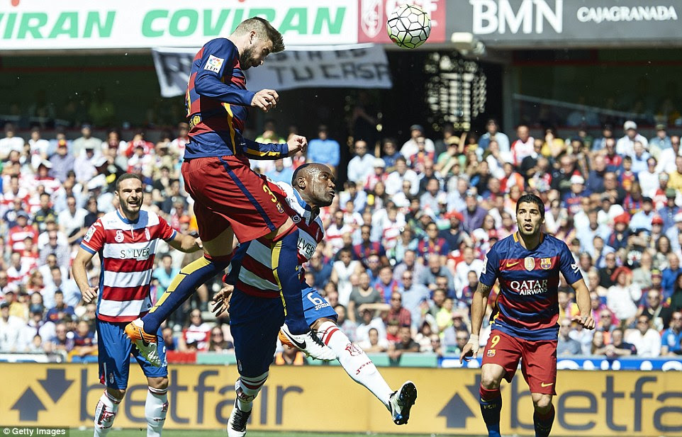 Spanish centre-back Gerard Pique rises highest to plant his head on the ball as he competes in the air with Granada's Doucoure