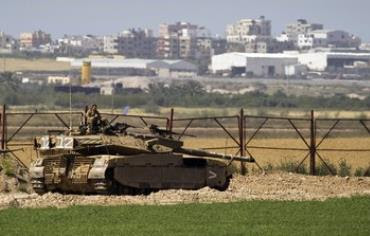 IDF soldier sits atop a tank just outside northern Gaza