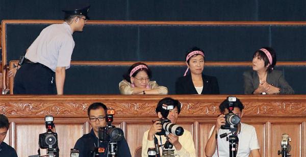 本会議中の傍聴席に「怒れる女性議員の会」のピンクのハチマキを巻いて現れ、注意を受けた辻元清美議員ら=18日午後、国会・参院本会議場(鈴木健児撮影)