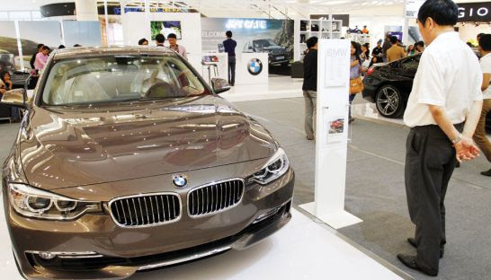 A potential buyer views a BMW on display at Aeon Mall in May 2014.