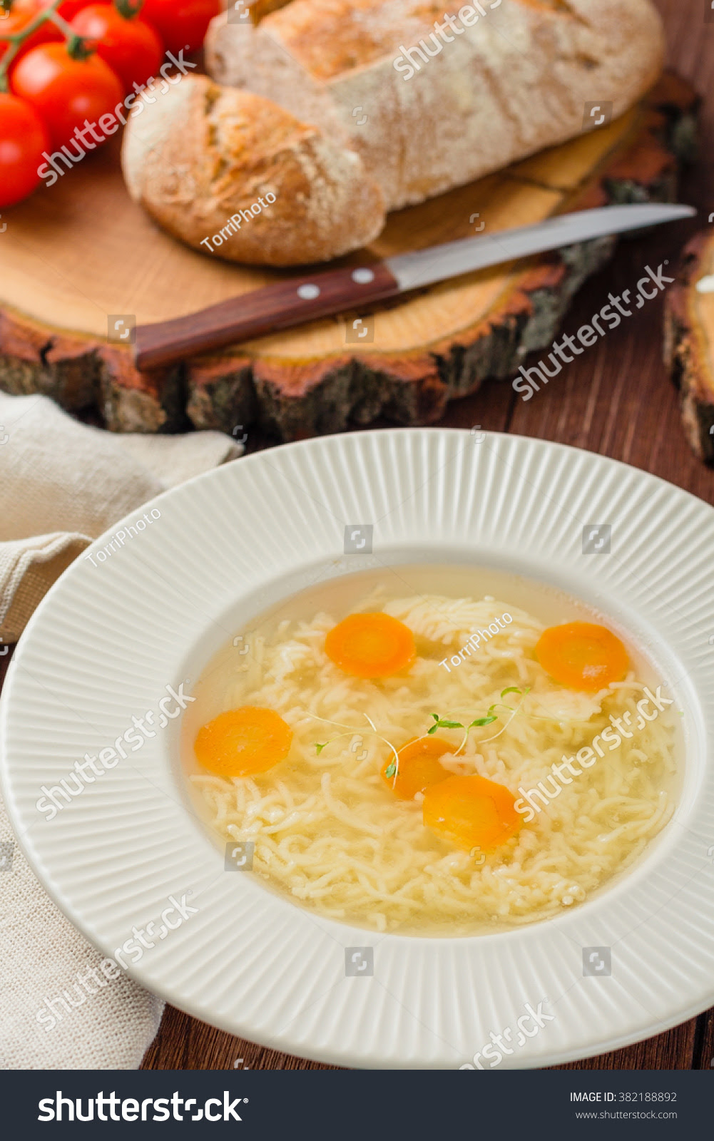 http://www.shutterstock.com/pic-382188892/stock-photo-chicken-broth-with-noodles-and-carrots-in-a-white-plate-on-a-rustic-wooden-background-shallow-focus.html