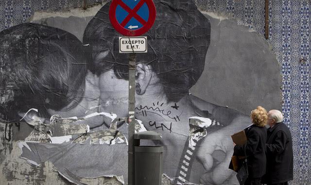 Una pareja de ancianos observa un grafitti donde dos jóvenes se besan