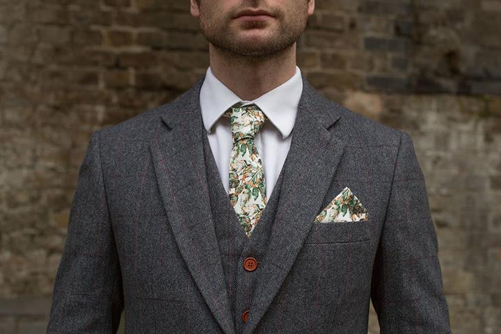 Wurde der Bräutigam trägt einen schicken grauen Anzug mit dünnen rosa Streifen, und einer handgefertigten Krawatte mit einem Botanischen print