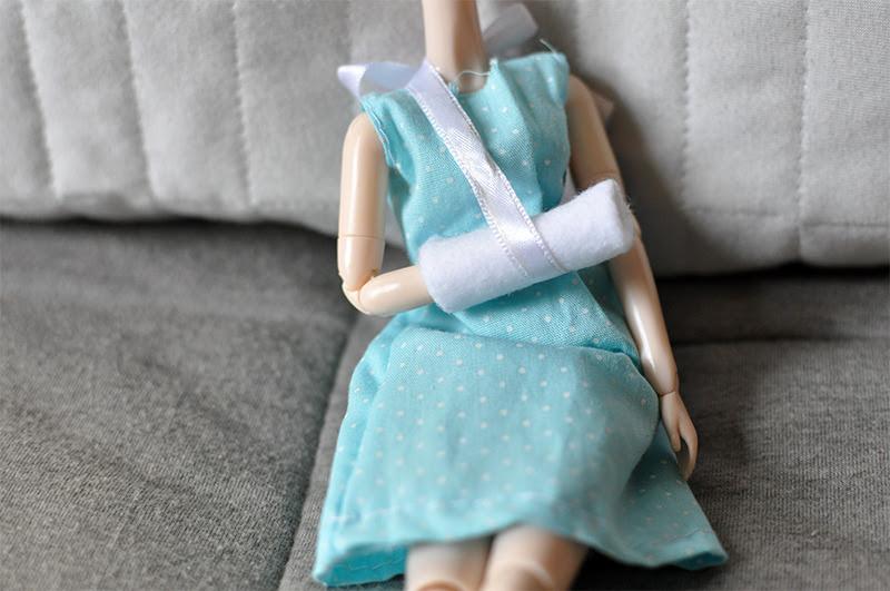 boneca com uma tipóia na mãozinha