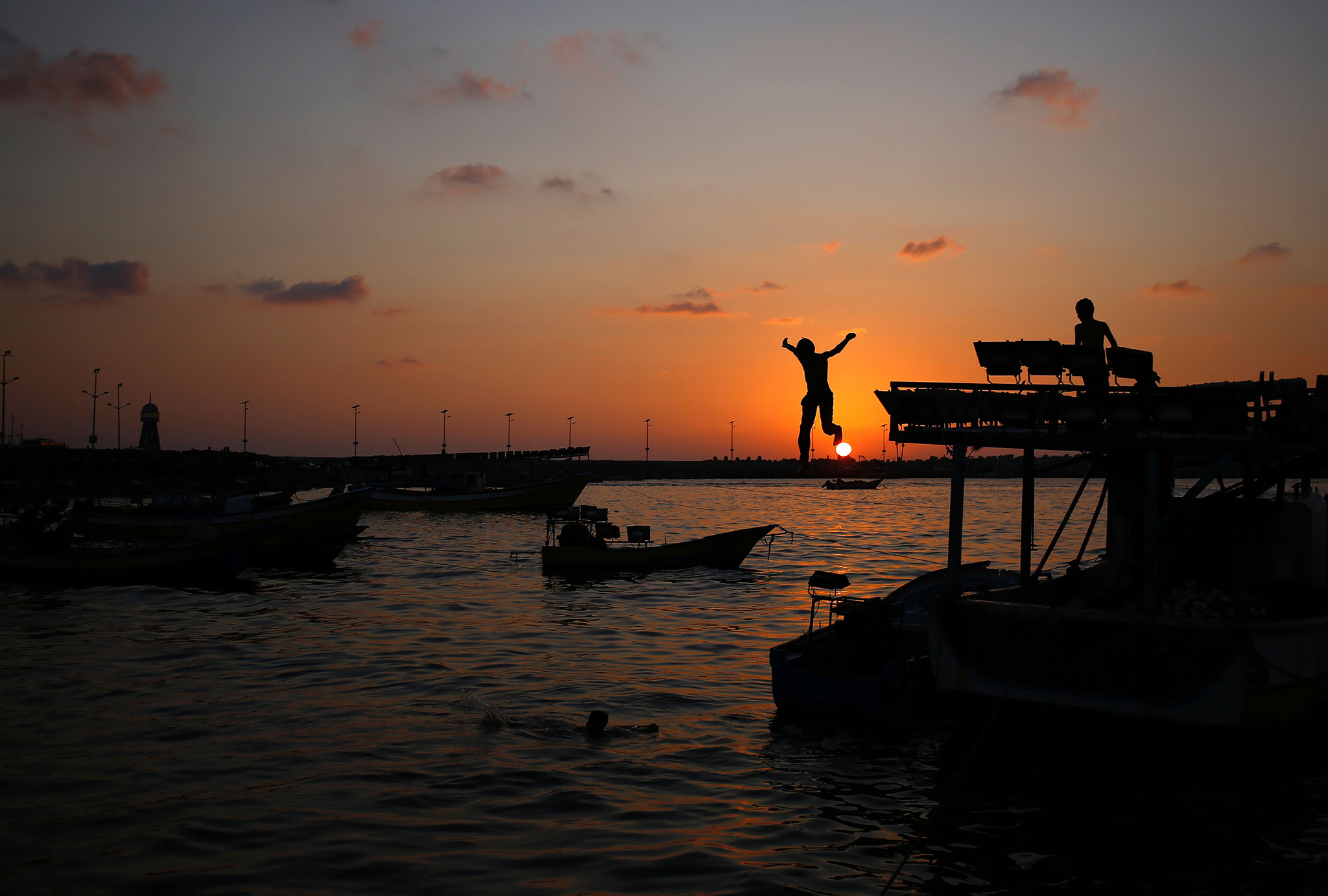 A boy jumps into the sea at sunset in Gaza City on August 11, 2016. / AFP PHOTO / MOHAMMED ABEDMOHAMMED