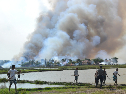 Ethnic Rohingya with weapons walking away from a village in flames while a soldier stands by. Rakhine State, Burma, June 2012. © 2012 Private/HRW