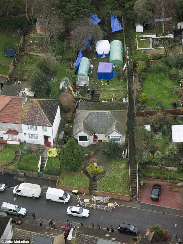 Aerial view: Two blue police forensic tents were erected in the rear garden of the family's three-bedroom bungalow in Pembrooke Road, Erith. Forensics can be seen combing the area for evidence, while reporters, pictured at the front of the house, line the street