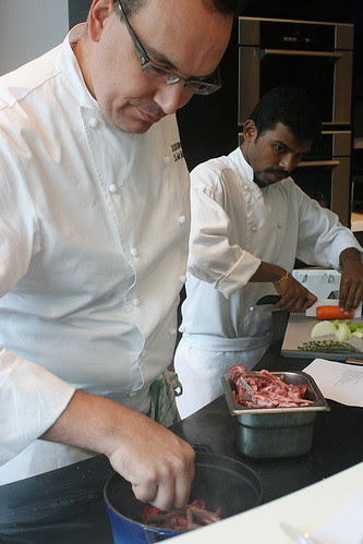 Chef Julien putting the lamb trimmings into a very hot pot, while assistant Balaji chops up the vegetables