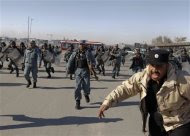 Afghan policemen run towards protesters during a protest in Kabul February 24, 2012.  REUTERS/Omar Sobhani