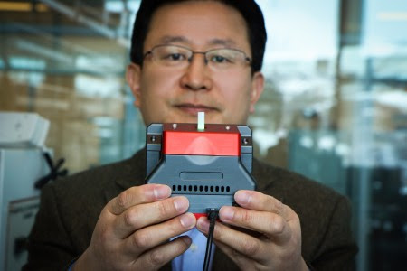 University of Utah materials science and engineering professor Ling Zang holds up a prototype of the new handheld leak detector