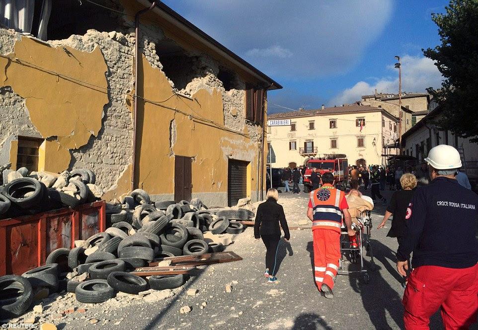 Rasto de destruição: Equipes de resgate e as pessoas a pé ao longo de uma estrada após um terremoto em Accumoli, onde uma família de quatro, incluindo duas crianças morreram