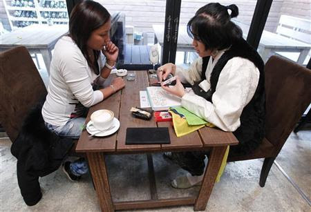 Japanese tourist Kumi Nemoto (L) consults fortune-teller Ilwol-doryeong, 33, at Funny Sculptor Fortune-telling Cafe in Seoul November 19, 2010. Fortune-telling has permeated South Korea's youth culture in the form of ''saju,'' or ''fate,'' cafes, where fortune-tellers tell customers in very specific terms about their possible jobs and marriages. KOREA-FORTUNETELLING/ REUTERS/Jo Yong-Hak (SOUTH KOREA - Tags: SOCIETY)