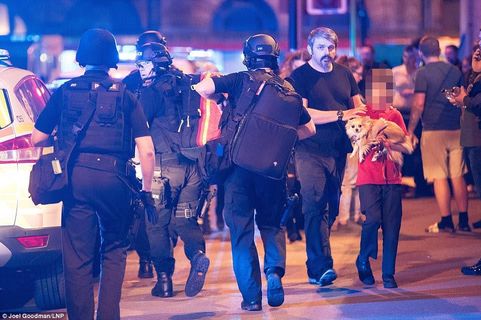 Um menino acompanhado por um adulto carrega um cão fora da arena, onde as multidões de polícias foram recolhidas.  A polícia de Greater Manchester disse que estará liberando um número de contato para povos faltando o mais cedo possível