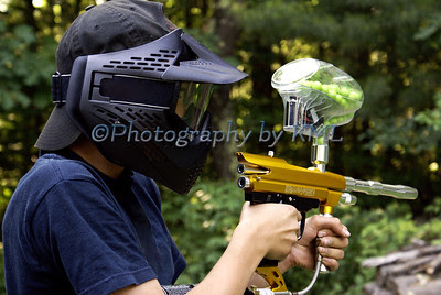 a teen wearing a paint ball mask and aiming a paintball gun