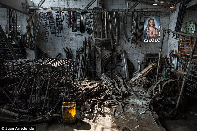 Icon: A painting of Sacred Heart of Jesus, the old name of the town, hangs in a workshop