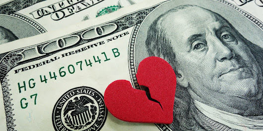 A broken red heart over two US hundred dollar bills