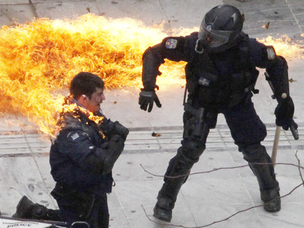 Um policial é atingido pelas chamas e seu colega tenta ajudá-lo. Bomba foi jogada por manifestantes nesta quarta-feira (23), em frente ao Parlamento em Atenas. (Foto: Reuters)