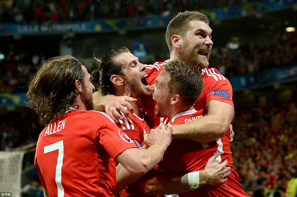 Wales striker Vokes is mobbed by team-mates Joe Allen, Bale and Gunter after his goal sealed an historic win