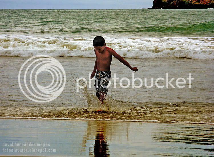 Niño en el mar chapoteando y salpicando agua