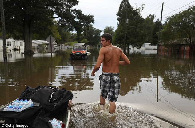 Tray Blazier pulls a boat as he helps a friend check in on his flooded home on Thursday in Sorrento