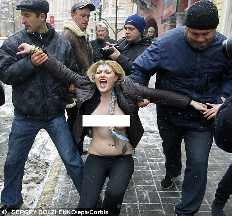 Ukrainian policemen arrest one of the activists protesting in Kiev