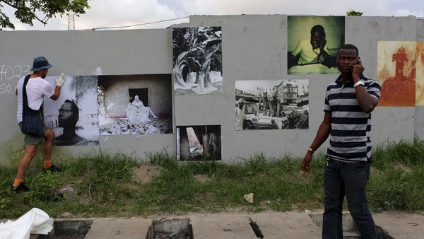 A pedestrian walks by as photographer Robin Maddock pastes a photograph on a wall for LagosPhoto festival in Lagos, Nigeria