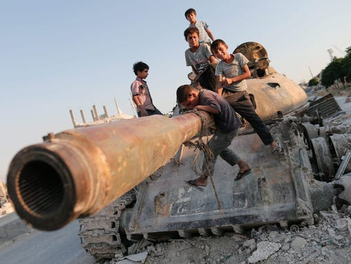 Syrian children play on a destroyed tank  south of