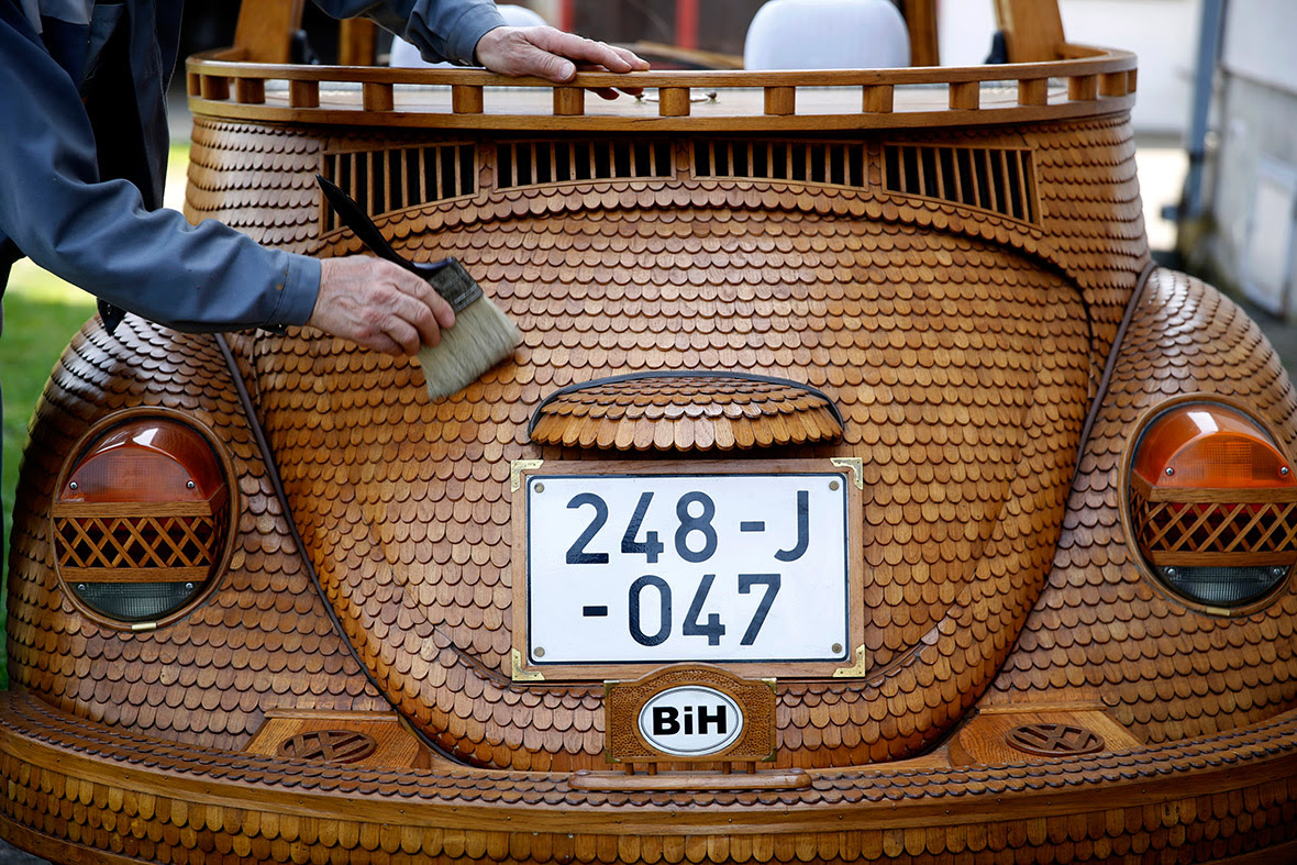 Momir Bojic, 71, cleans his wooden Volkswagen Beetle in front of his home in Celinac, near Banja Luka, Bosnia
