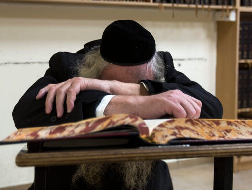 An elderly Jew is in deep prayer in the main hall of