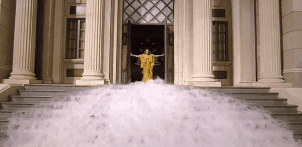 Beyoncé emerge de um templo cercado com água da mesma maneira um bebê sai do útero após as quebras de água.