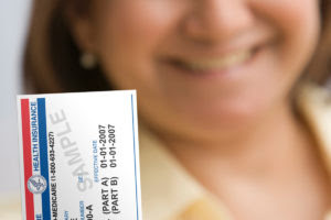 A woman holds up a Medicare card