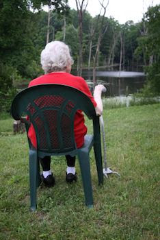 Older woman sitting looking at a stream