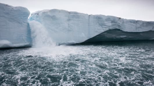 Melting water pours from ice face of Brasvellbreen Icefield on stormy summer morning.