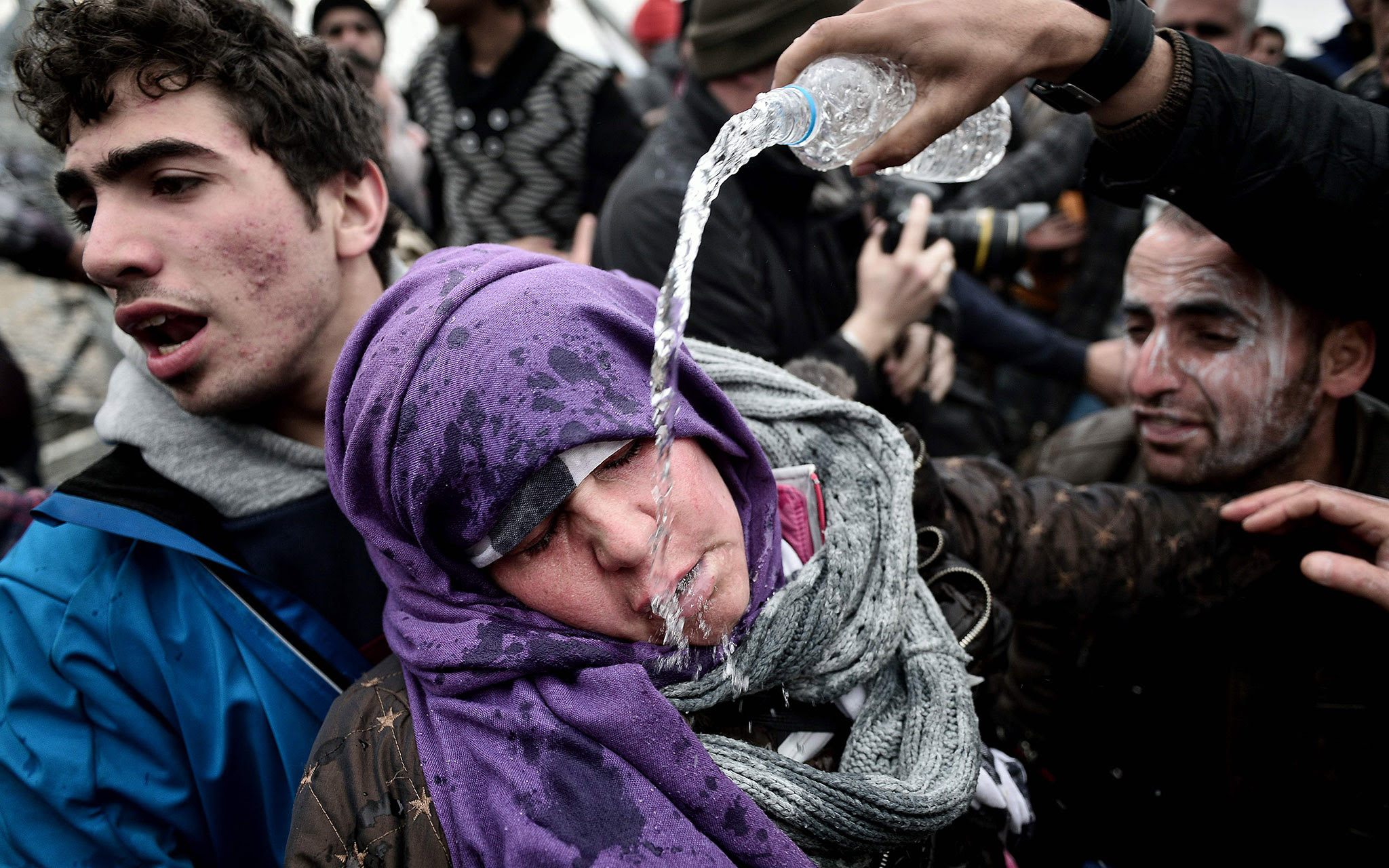 A refugee pours water over a woman who collapsed after losing her child during a mass panic after Macedonian police used tear gas against refugees at the Greek-Macedonian near the village of Idomeni.