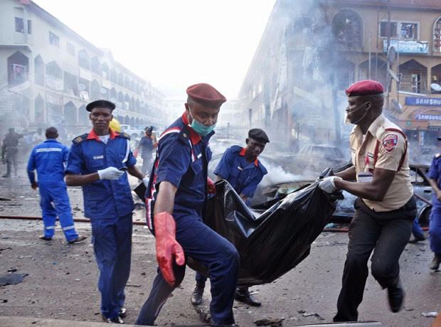 Policiais carregam corpo em saco plástico após explosão que deixou mortos em Abuja, na Nigéria, nesta quarta-feira (25) (Foto: Gbemiga Olamikan/AP)