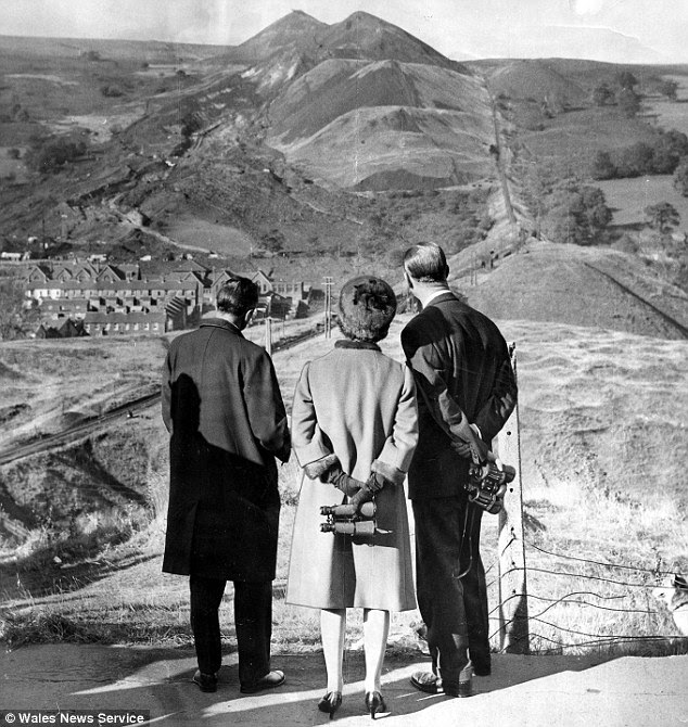 Paying their respects: The Queen and Duke of Edinburgh look towards the landslide during their visit in 1966 after the disaster