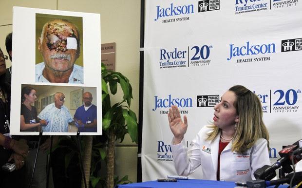 A cirurgiã plástica Wrood Kassira, do Jackson Memorial Hospital, exibe imagens de Ronald Poppo, que teve rosto devorado por ataque canibal, durante entrevista nesta terça (12) (Foto: Wilfredo Lee / AP)