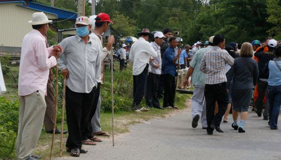 Cambodian People's Party supporters stand on the side of the road holding bamboo sticks