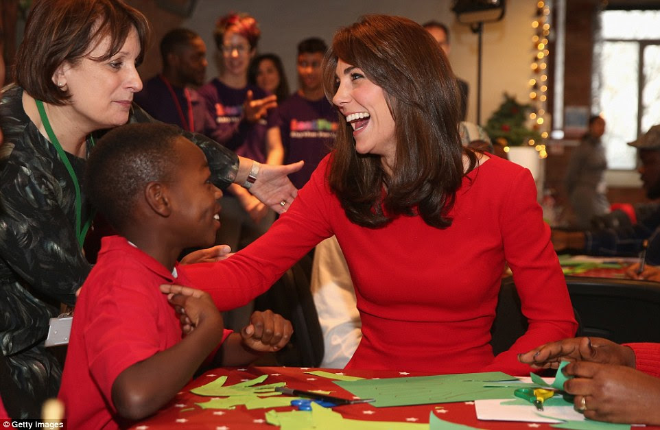 The Duchess warmly patted the little boy on the shoulder while a member of the Anna Freud centre staff looked on