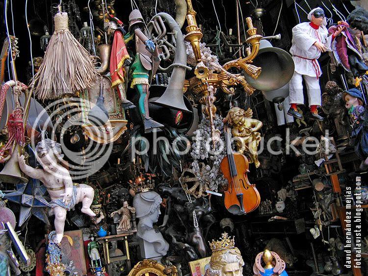 Pequeños y medianos objetos de todo tipo colgados de forma abigarrada en una tienda de Nápoles