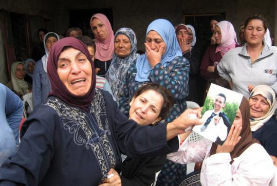 The mother of a Lebanese soldier displayed a picture of her son as she mourned his death outside her house yesterday.