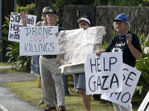 Protesters hold signs as the motorcade of U.S. President Barack Obama returns to Obama's vacation home in Kailua, Hawaii December 28, 2013. REUTERS-Kevin Lamarque