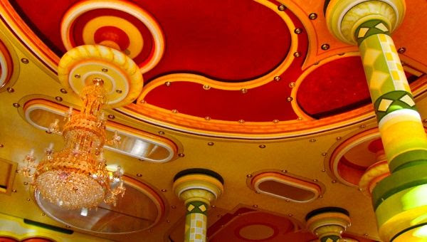 Bright colors and a lavish chandelier distinguish this ballroom ceiling