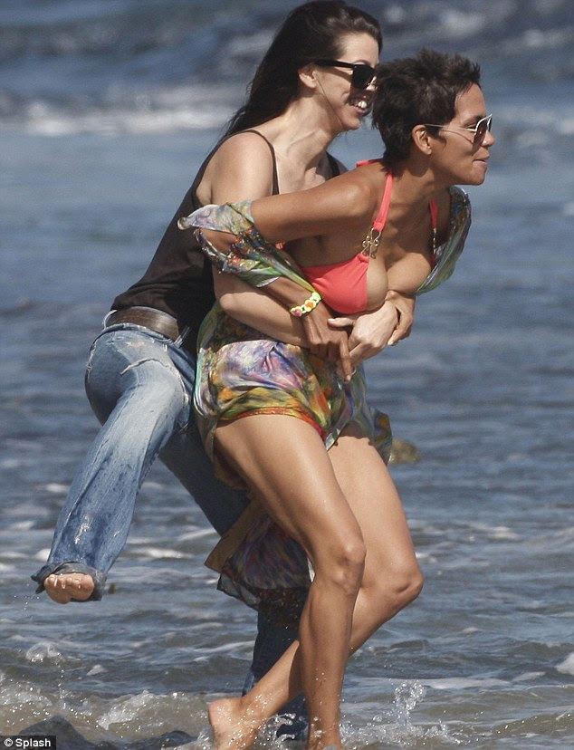 Grapple: A laughing Halle Berry was wrestled into the sea by her female friend on the beach in Malibu yesterday as she celebrated her 45th birthday