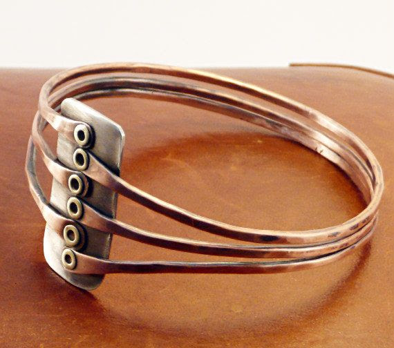This handmade bracelet is made of 12 gauge copper wire and sterling silver. Each bangle is cold connected to a piece of sterling silver. The length of the silver center piece is 3.1 cm (1.20 inch) and is 1.5 cm wide (0.58 inch).