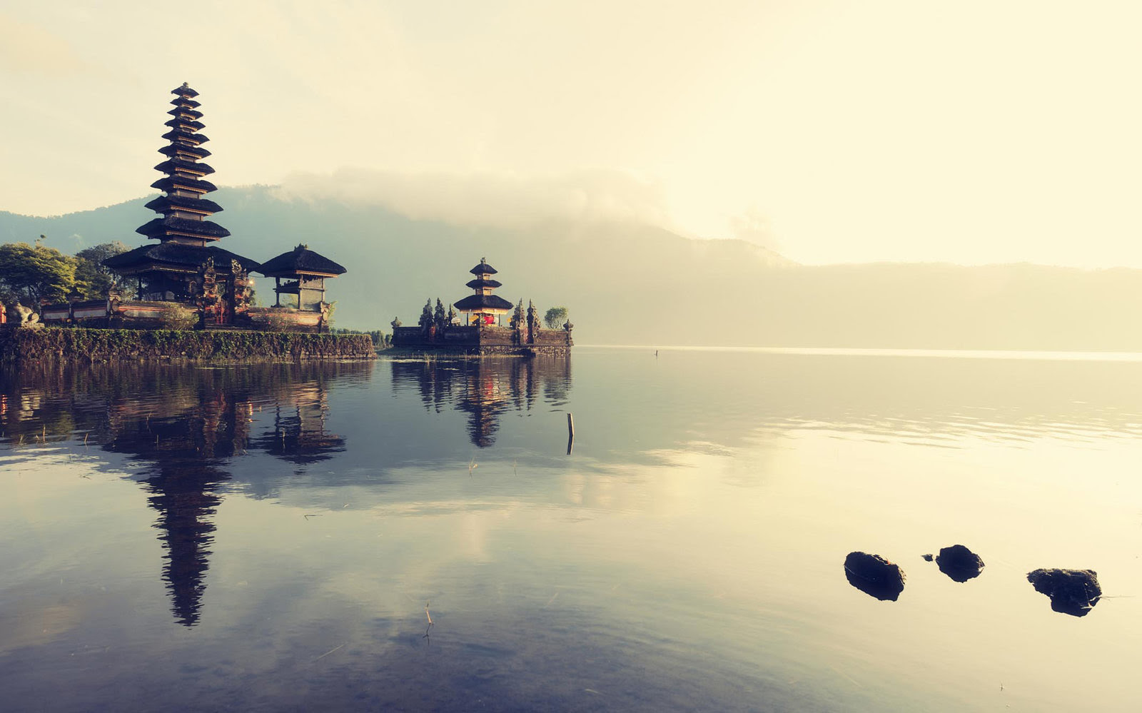 Sunrise over Pura Ulun Danu Bratan (Balinese floating temple on lake Bratan) with mountains in the background and clear reflections on the lake.