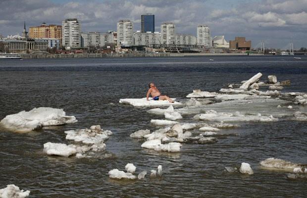 Russo toma banho de sol sobre um bloco de gelo no rio Yenisei, em Krasnoyarsk (Foto: Ilya Naymushin/Reuters)