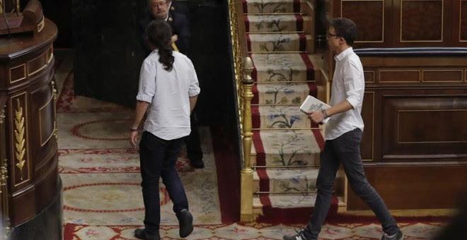 """El líder de Podemos, Pablo Iglesias (i), y el portavoz parlamentario de Unidos Podemos, Íñigo Errejón (d), abandonan el hemiciclo en protesta por unas palabras del portavoz del PP, Rafael Hernando, que ha acusado a Pablo Iglesias de """"usar el nombre de Esp"""